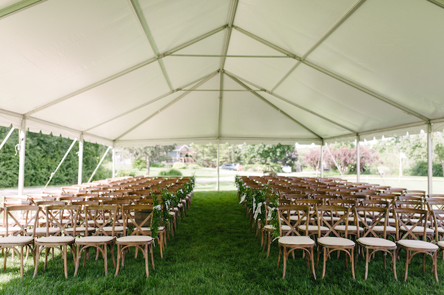 Happenings Party Rentals Underneath a 30x60 NaviTrac Frame Tent Equipped With Crossback Chairs